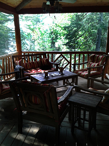 covered porch with adirondack style furniture